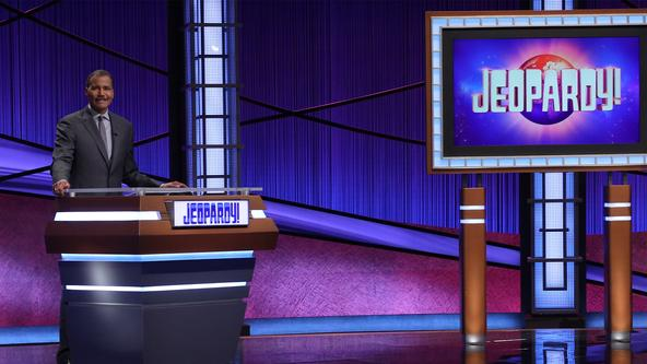 Bill Whitaker on the Jeopardy! set, behind the lectern.